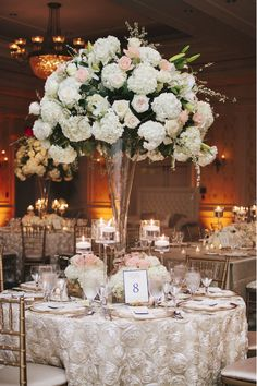 Caitlin and Chase's wedding guests sat at ivory reception tables surrounded by golden chairs. Tall centerpieces featured white and pink hydrangeas, roses, and lilies atop glass trumpet vases. #centerpiece #flowerarrangement #candles #lighting Photo by: Millie Holloman Photography