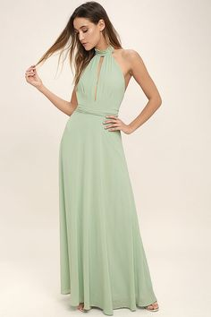 Endless romance always follows an appearance of the First Comes Love Sage Green Maxi Dress! Woven poly sweeps from a ruffled, halter neckline into a backless bodice with pleated detail and a keyhole cutout. Tying sash wraps around the waist above a cascading maxi skirt. Hidden back zipper/clasp.