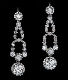 Art Deco Diamond Platinum Long Earrings, 1920s. The earrings are crafted in platinum and 18K white gold. They are set with two large bright white and sparkling old European cut round diamonds of 2.55 and 2.15 carats, plus 44 antique cushion, old European, single and rose cut diamonds; total diamond weight 7.76 carats.