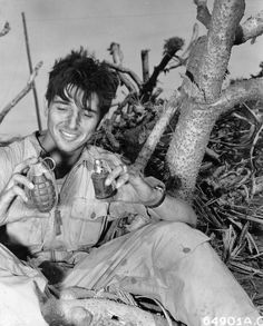 Lt. Joseph D. Goons, 1295 Rademacker Street, Detroit, Michigan, holding two hand grenades picked up after Japanese banzai raid on Iwo Jima, Bonin Islands. The one in his left hand is of Japanese make and the other is American.