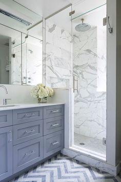 Gorgeous marble tiles & built in vanity. Lovely chevron floor ties it all in.