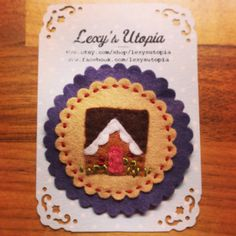 Sweet little alpine cottage brooch handmade using wool felt and embroidered. Measures roughly 2 inches in dia and presented on a Lexys Utopia card x