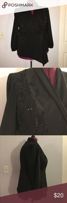 """eShakti Black Sheer Beaded Wrap Top size 2X Up for grabs is this blouse from eShakti. It is a size 2X / 22W and measures 28.5"""" from shoulder to hem and has a 49"""" bust and a 36"""" waist. This top is a wrap style in a sheer black fabric. It has a shawl collar and ties over the left hip. This blouse features a beaded and sequined vine and leaf design on the front. It has been gently worn and is in excellent condition. eshakti Tops Blouses"""