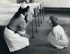 British psychiatric nurse in a children's mental hospital in the 1960s remonstrating with a straitjacketed young male patient.