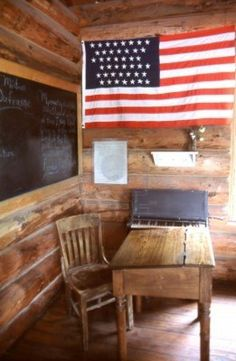 This depicts everything Americana..log  cabin, one room school house, and Old Glory!  Love this.