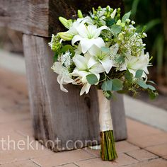white bouquet of lilies, wax flower, eucalyptus and hypericum berry.
