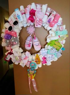 Diaper Wreath, instead of the same old diaper cake. Shower guests were in awe over this wreath, contains loss of goodies for the mom to be! Decorated with onsies, washclothes, pacifiers, toiletries, hand sanitizer, sunglasses, baby toys, hair bows and flowers and shoes hanging in the middle! So fun to make, attatch diapers with ribbon to a $5 wire wreath frame found at your local craft store. Baby items attached with clear rubber bands.