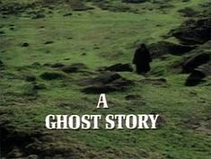 """A Ghost Story for Christmas - The image is the title screen of the adaptation of """"The Signalman"""". A lone traveller, wearing black Victorian travelling garments and silhouetted so that he cannot be identified, treads across green fields pockmarked by molehills. He is walking towards the camera. A slightly muggy, cloudy atmosphere pervades the image. The strand title """"A Ghost Story"""" is superimposed over this in bold, white capital letters."""