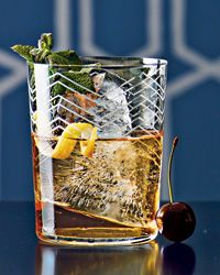 La Florida Rum Daisy  2 ounces white rum 1/2 teaspoon yellow Chartreuse 1/2 teaspoon Simple Syrup Dash of Angostura bitters 1 mint sprig, 1 spiral-cut lemon twist and 1 or 2 cherries, for garnish