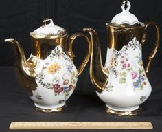 CHINA BEAUTIFUL AND STYLISH BAVARIAN TEAPOTS BY KLEIBER DECORATED IN 22 KARAT GOLD AND FLORAL DESIGN. MADE IN GERMANY. MEASURES 11 IN. TALL AND 9 IN. TALL.