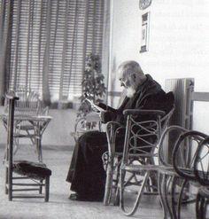 Seduto nella veranda, Padre Pio legge una lettera