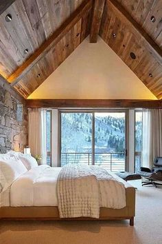 Love this bedroom...reclaimed wood ceiling and beams with a stone accent wall!