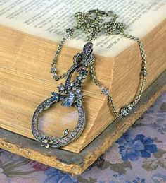 """Magnifier Pendant - Eyewatering coloured glass stones are meticulously set within a vintage reproduction magnifying glass that dangles prettily on blouses while awaiting the call to decipher fine print on sales tickets, menus and programs. 4"""" pendant dangles on a 32"""" chain."""