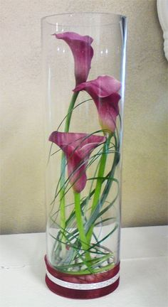 Calla Lilly Centerpiece. Instead of purple callas we could do orange lillies? With a floating candle on top, of course.