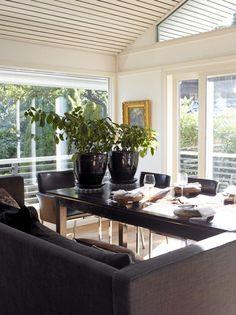 Store vindusflater slipper mye lys inn i spisestuen. Mens vegger og tak er holdt hvite, er møblementet i mørk grå og svart, som gjør selve spiseplassen litt lunere. På den ene siden av bordet, har beboerne valgt å plassere en sofa, som gjør det behagelig å sitte under lange middager. Styling: Tone Kroken.