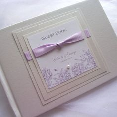 Wedding Guest Book.  Floral Purple Print and Lilac Satin Ribbon and Pearl. Personalised & Custom Made. £30.00, via Etsy.