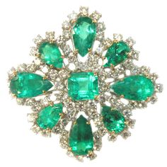 Brooch featuring 1 emerald Cut and 8 Pear Shape Emeralds of columbian origin weighing 20.78 Carats with Round diamonds weighing 7.42 carats in a 18K white and Yellow gold.