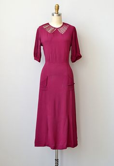 1930s deep cranberry red dress with illusion cut-out collar. Short set in sleeves, gored skirt with inverted pleats along the hem, and small patch pockets with fold-over flap.