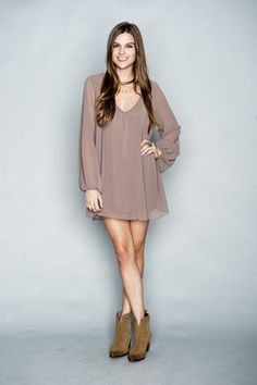 The Mumu Donna Michelle Tunic in Dune features a solid tan color, flowy silhouette, and long sleeves with a v neckline.