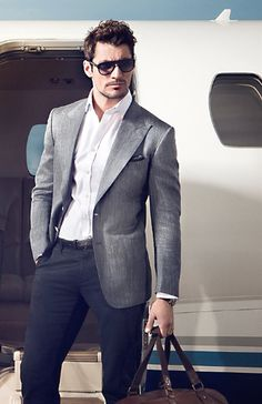 Picture of success in Aviator style sunglasses, blazer, white button down, and navy pants,