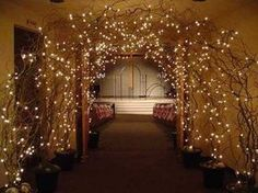 beautiful entrance-naked trees in pots with gravel and spray foam, add extra curly willow branches for fullness and white lights.