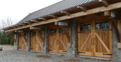 A large garage sports carriage house doors with traditional hardware. A large garage sports carriage house doors with traditional hardware. Glass Garage Door, Wood Garage Doors, Barn Garage, Garage Plans, Garage Ideas, Timber Frame Garage, Timber Frame Homes, House Doors, Carriage House