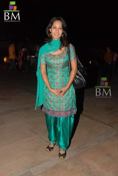 Bollywood actress in green and embroidered work Kameez paired with Indian regular salwar with round neck pattern.