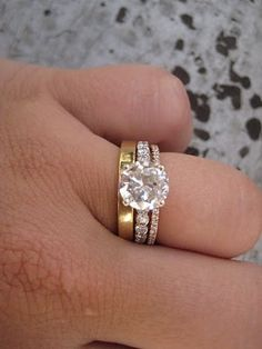 A mix of a white gold engagement ring and a yellow and diamond gold wedding bands