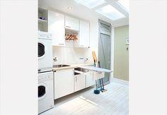 Lavanderia esteticamente integrada aos outros ambientes da residência. A porta de acesso é de aço escovado e vidro jateado. Armários com espaço para a roupa suja, a limpa e a passada. A tábua de passar dobrável fica armazenada em uma gaveta  Arquivo / Casa e Jardim