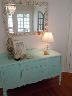 shell mirror, corral as work of art, and blue hawaiian skies vintage dresser.
