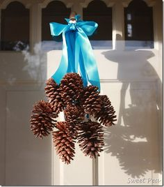 Pine Cone Door Decoration. I had something similar when I moved here to TN. My Dad had made a pine cone Christmas deco from Red Wood pine cones (they were huge). Someone stole them off my door my 1st Christmas here in TN.