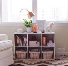 Darling shelf styling in this storage cube in a boho chic nursery!