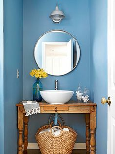 blue in the bathroom -  love the round mirror and sink and vanity