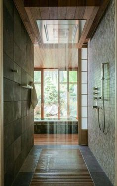 East inspired walk in shower with wooden floor and a rain shower