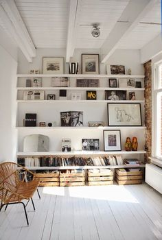 Full wall of shelving. Propped up art. Wooden crates for storage. Oh, and white floor boards. Of course!
