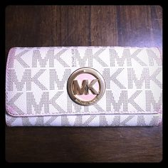 Mk wallet Cream with brown MK monogram wallet. Four Bill pocket holders and one zip up in the middle. 16 credit card holders. perfect working condition only flaw is the red stain around the wallet. Michael Kors Accessories
