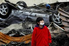 JAPAN/ A boy looks on in front of an overturned car among debris in Otsuchi, Iwate prefecture March 21, 2011, after an earthquake and tsunami hit the area on March 11. REUTERS/Aly Song (JAPAN - Tags: DISASTER ENVIRONMENT)
