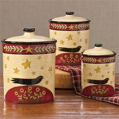 """Hand Painted """"Sunflower & Crow"""" Canister Set ~ Teresa Kogut designed our country classic Folk Crow ceramics. With rich red, basic black and gold combined in a folk friendly format, the design coordinates beautifully with many of our country textiles. Design by Teresa Kogut. Hand painted on high fire dolomite. Dishwasher and microwave safe. Dimensions: Small 6.5""""H x 4.75""""Dia, Medium 7.5""""H x 6¼""""Dia, Large 9""""H x 7""""Dia. Material: High Fire Dolomite. Set of 3. Gaskets included for air tight seal."""