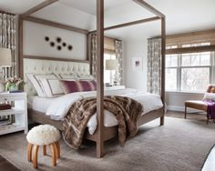 Simplistic style makes this room livable. Neutral browns with a hazy pink-grey undertones are soothing hues for this muted and subdued bedroom. The heavy fur throw breaks up the white comforter and connects brown tones of the rug to the canopy bed overhead. Feminine touches grace orchid accent pillows and bronze wall sculptures. Color of the year, marsala peeks out of paintings, throws, and accents. With plenty of plush pillows creature comfort rules this bedroom.
