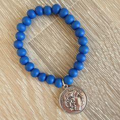 Armband van 8mm koningsblauw hout met metalen romeinse munt. Van JuudsBoetiek, €3,50. Te bestellen op www.juudsboetiek.nl.
