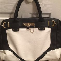 JustFab Manhattan Handbag JustFab black and white Manhattan Handbag. Faux leather with light gold hardware. Top zipper closure.  This handbag was only carried once but has 3 small light stains on the front of the bag from sitting in my closet laying against another handbag. JustFab Bags
