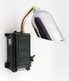 A wall light featuring a vintage cast iron fuse box, copper pipe neck and a signature fire extinguisher shade.