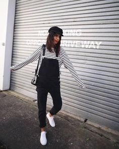 Perfect Blogger Spring Style On Trend Black And White Tone Themed Outfit Black And White Striped Long Sleeved Top Black Denim Dungarees Overalls Summer White Sneakers And Black Fisherman's Cap
