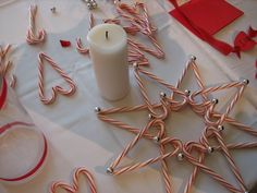 DIY:  How To Make A Candy Cane Centerpiece - candy canes, hot glue, beads and a pillar candle are all you need to make this cute centerpiece.  I think it would look great hung up, as long as it's stationery.