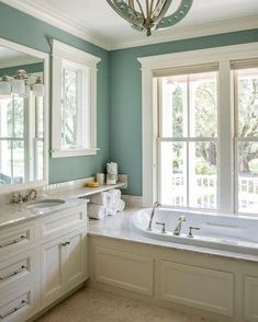Gorgeous, traditional bathroom with blue walls, a built-in tub, white cabinets, marble countertops and additional storage above the tub | Cameron & Cameron