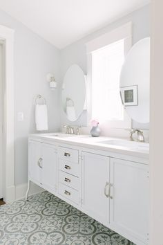 white vanity, patterned floors, oval mirrors, sconces