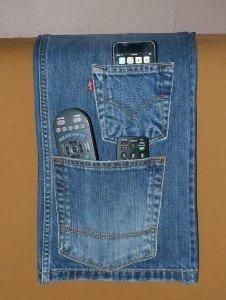 "Old made new - refashion jeans into novel and trendy remote holders. Simply cut off the legs of a pair of jeans, stitch the leg area closed and attach some velcro to the waist to form a closable bag. Then stitch a rectangle of fabric onto the one side of the waist area, which can be tucked between the mattress and your bed's base – this allows the denim ""shorts"" to hang out, forming  a cute organizer for remotes, glasses or TV guides."