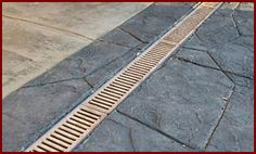Add a channel drain across a driveway. Then add a french drain/water diversion system out into the yard to disburse the heavy flow of water. Mother nature irrigation!