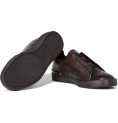 Ermenegildo Zegna's signature 'Couture' sneakers are distinguishable by their crosses - note the configuration of the elasticated front straps and the embossed 'xxx' emblem on the rubber heel patches. This pair has been constructed in Italy from leather in an elegant dark-brown hue. Wear them with indigo denim or grey tailored trousers.