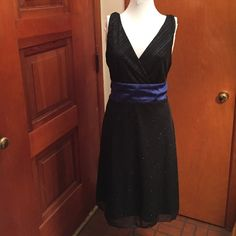 George Black & Blue Sparkle Sleeveless Dress XL A beautiful dress in a size XL by George, this is a black chiffon dress with an under layer with streaks on blue metallic sparkle. The dress is a midi length. It's sleeveless and has a satin ribbon belt that I believe ties in the back, but it may tie at the side. The top is a wrap design so it goes into a v-neck. George Dresses Midi